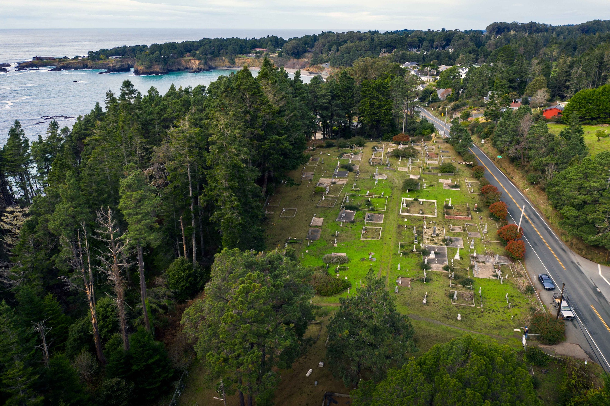 This is an aerial photograph of the Little River Cemetery with a view of the Pacific Ocean in the background and California Route 1 in the foreground.