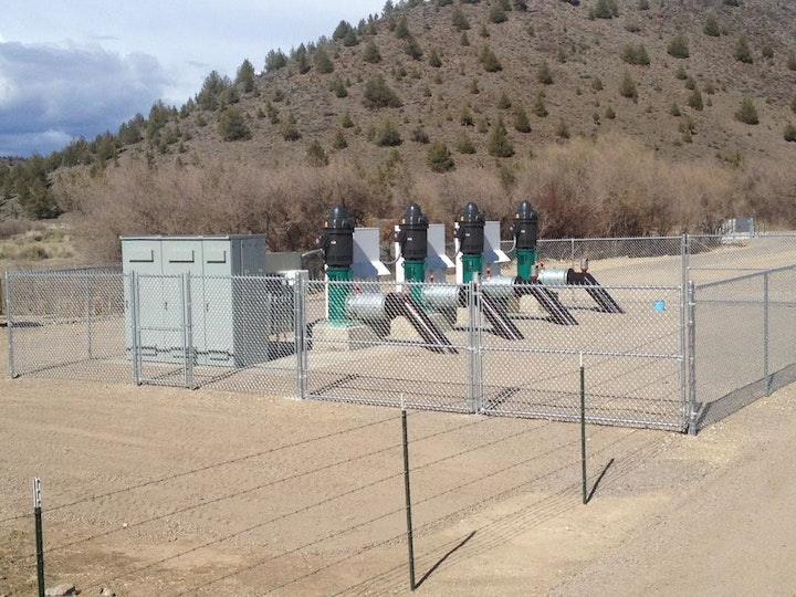 Irrigation pump station; 4 pumps surrounded by fence, mountain in background