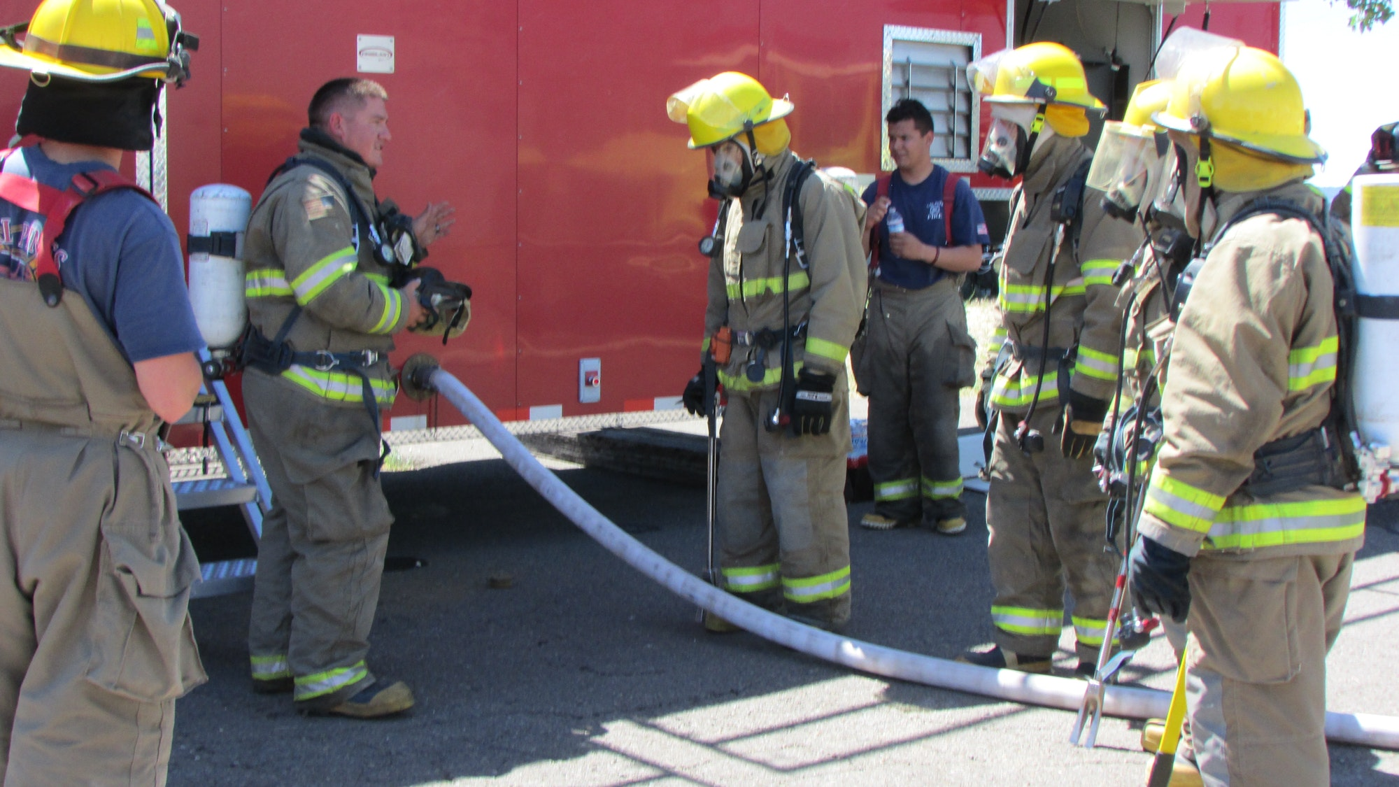 Assistant Chief Ryan Sherer showing the firefighters the in's and out's of  the Burn Trailer