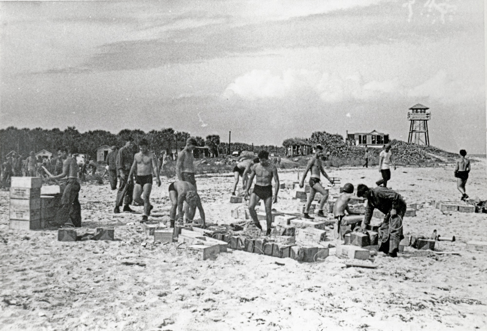 military service men working to move supplies on the beach with the tower in the background