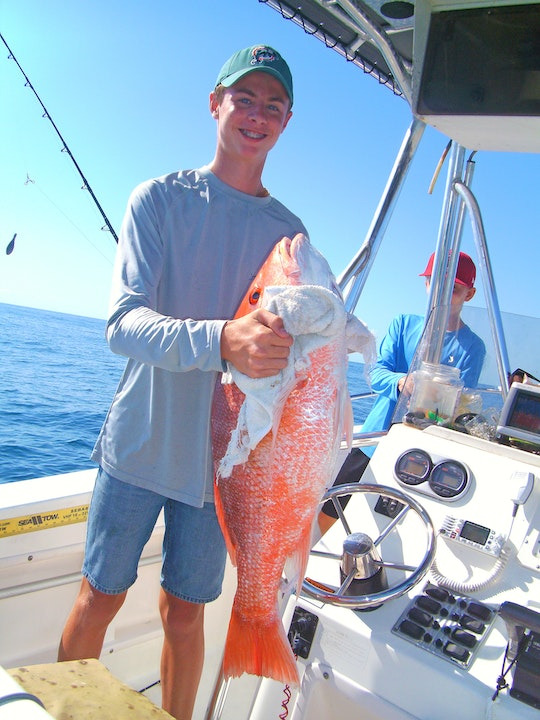 Teenage boy on boat holding large red snapper