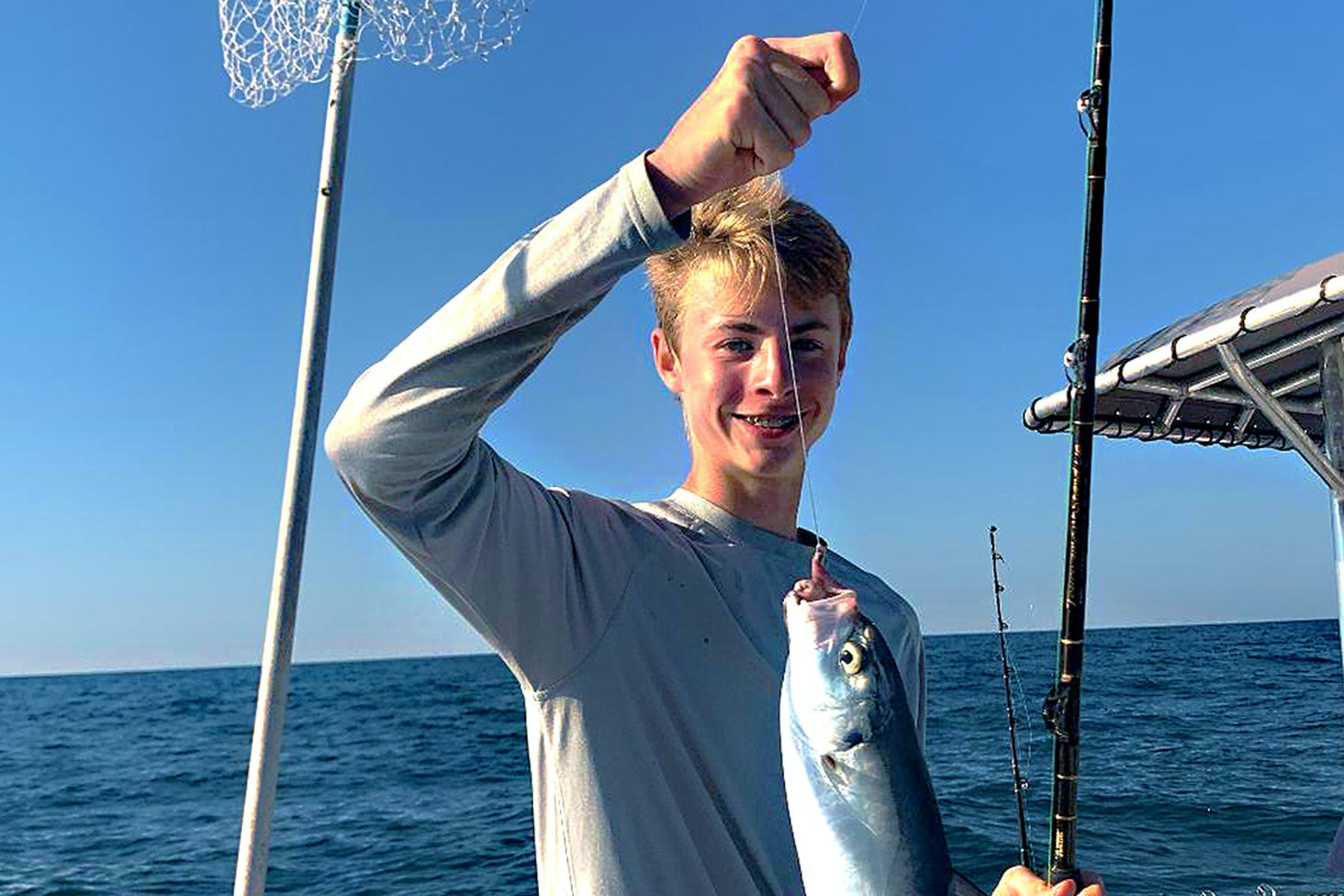 Teenager holding hooked fish on line