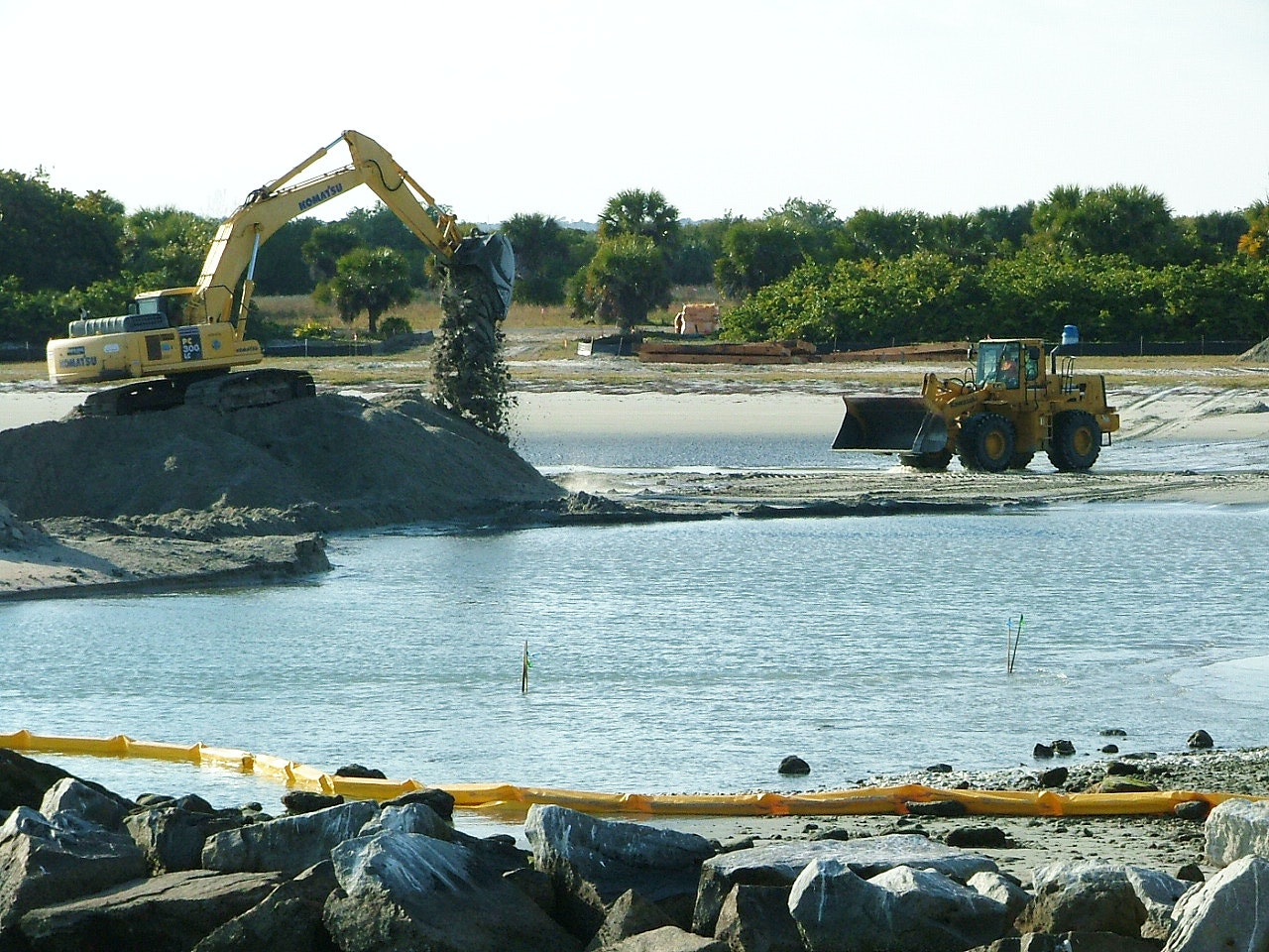 heavy equipment moving sand from tide pool