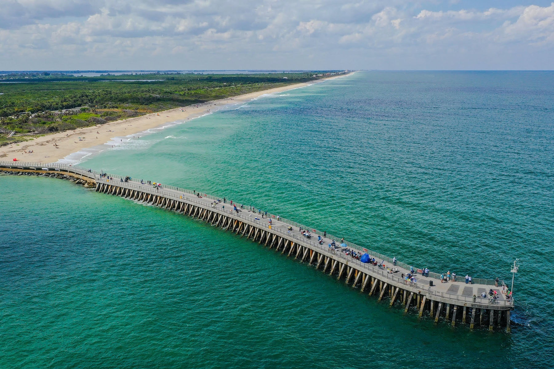 aerial view of jetty jutting out into the ocean