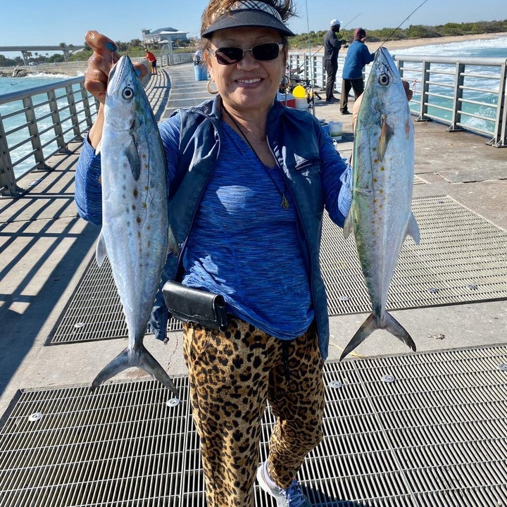 woman holding two spanish mackerel on the north jetty