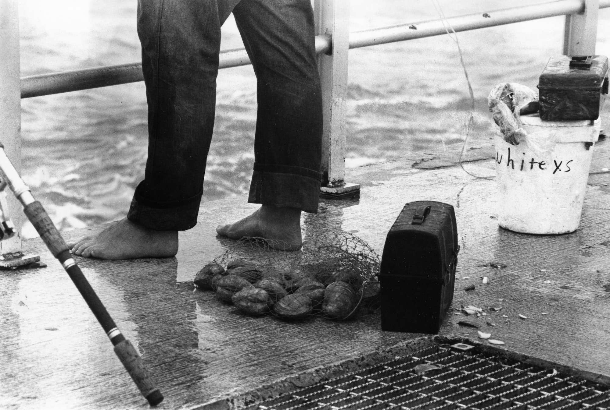 fisherman feet on north jetty with Whitey's bait buck, bag of clams, lunch pail and rod