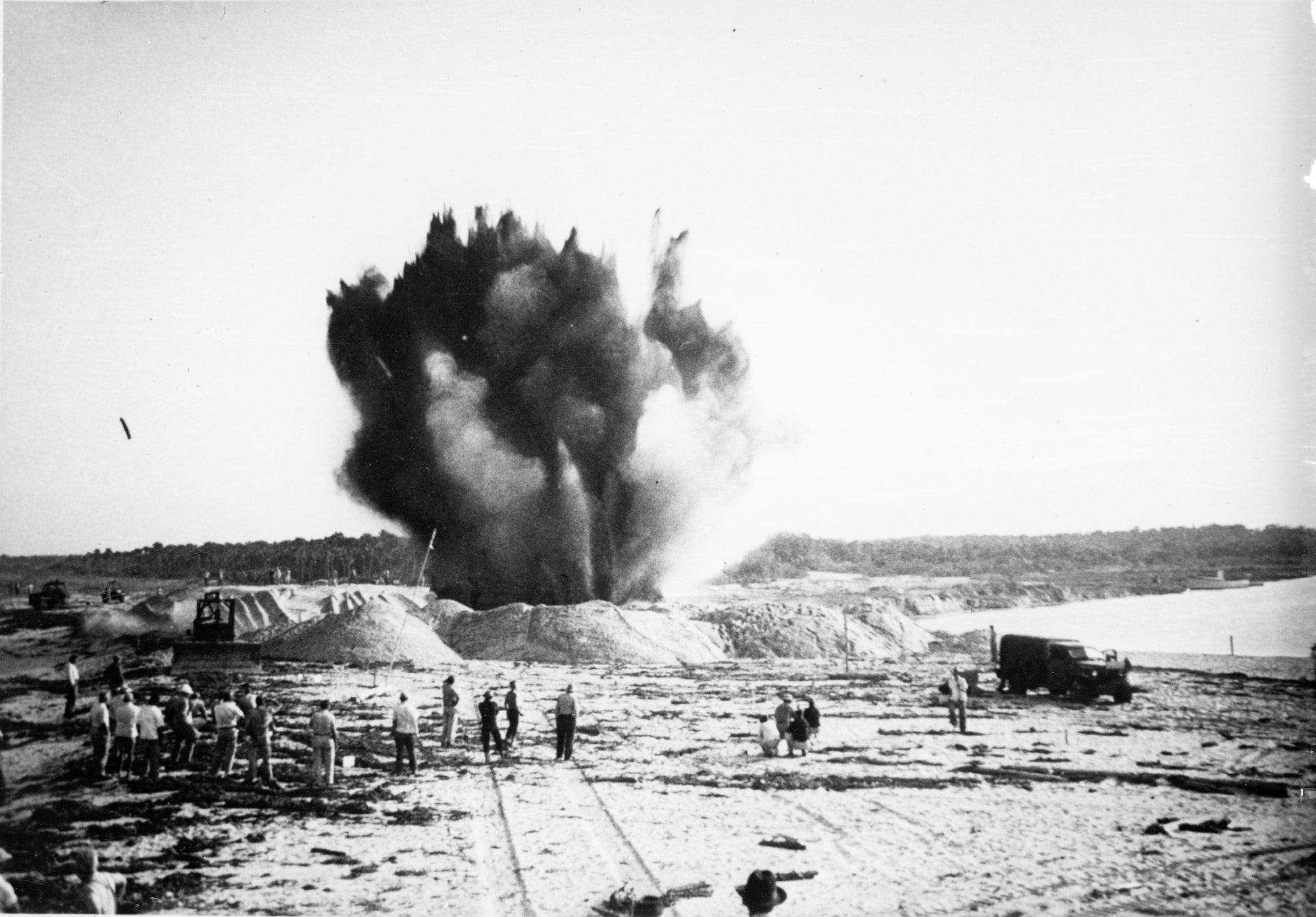 Wide view of dynamite blast of the last plug of sand between the Indian River and waters of the Atlantic Ocean with construction crews looking on