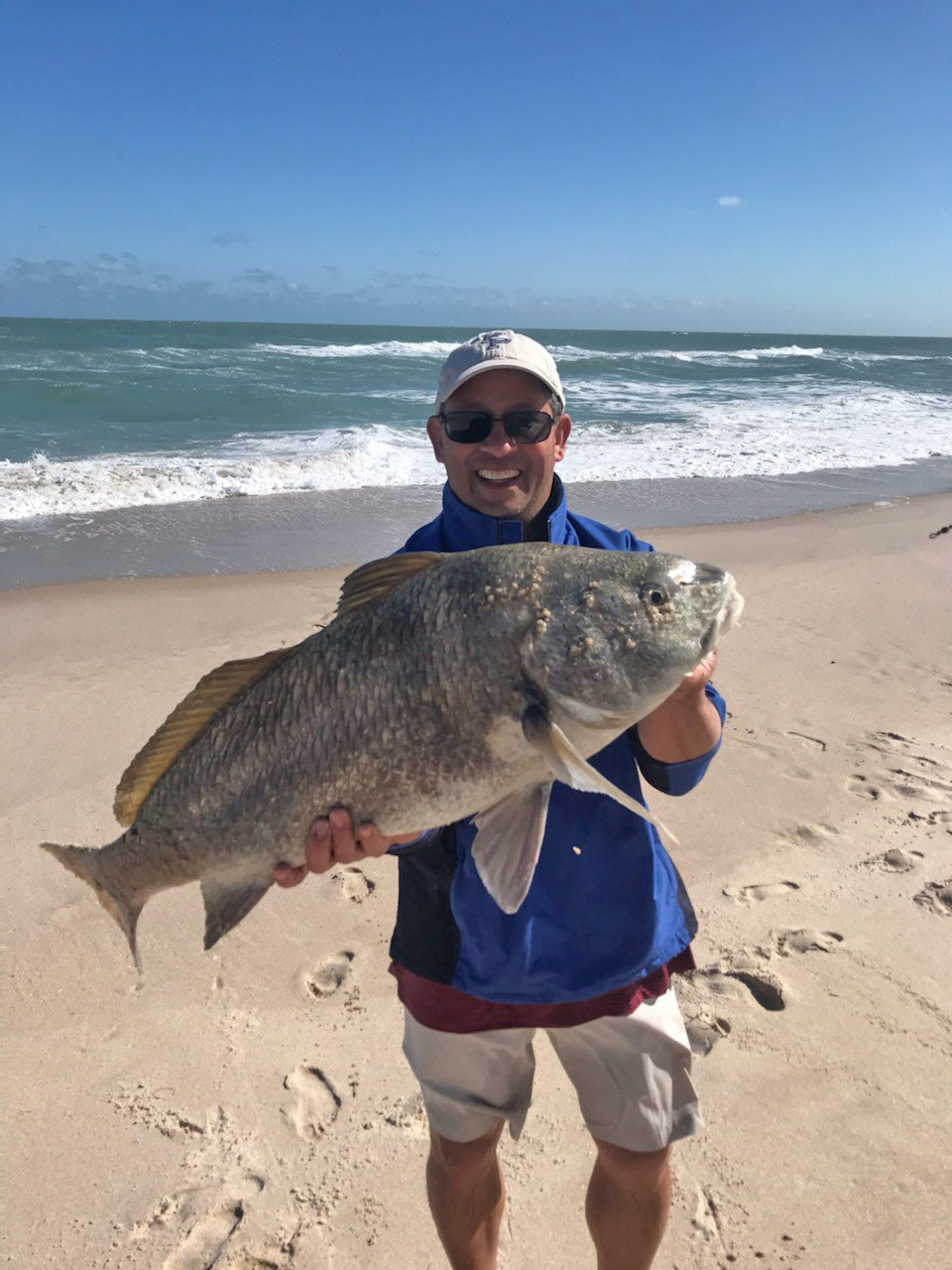 man holding large fish standing on beach