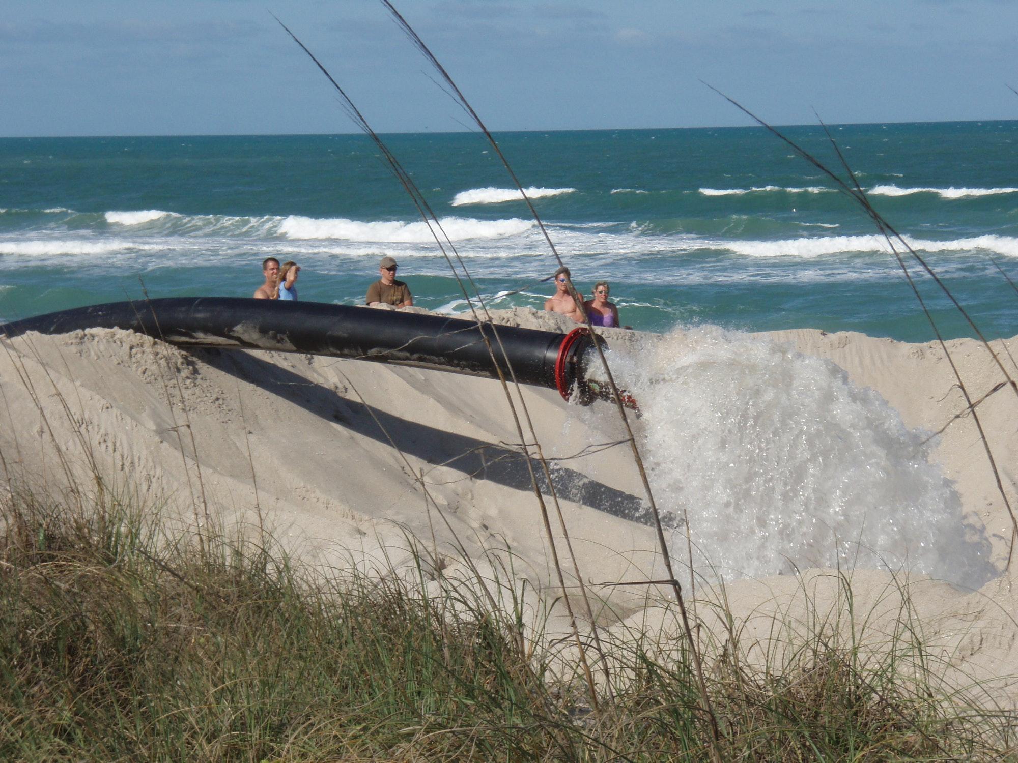 beachgoers watching dredge pipe pump water into dike