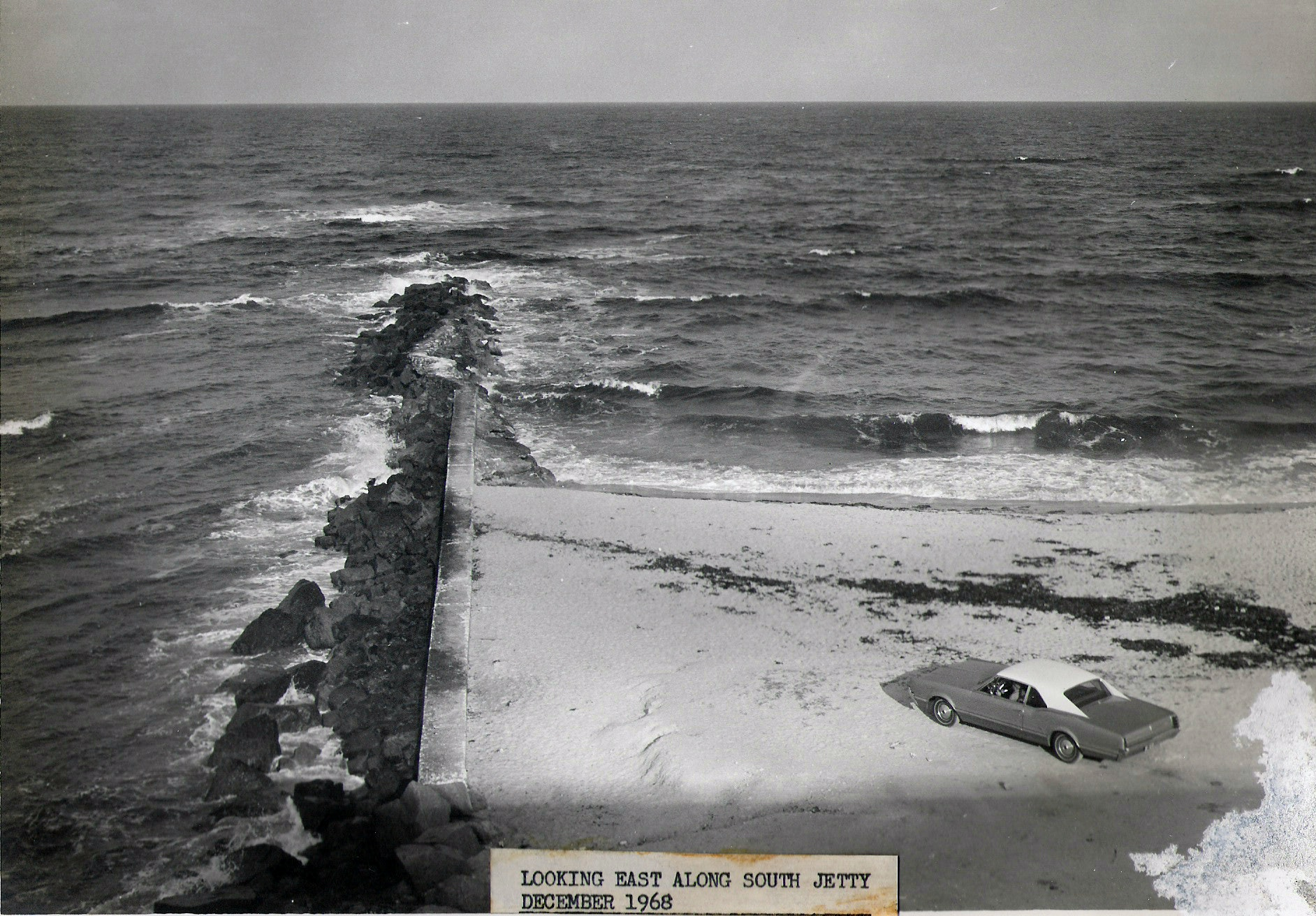 1968 view of south jetty looking East with car on beach shore at base of jetty