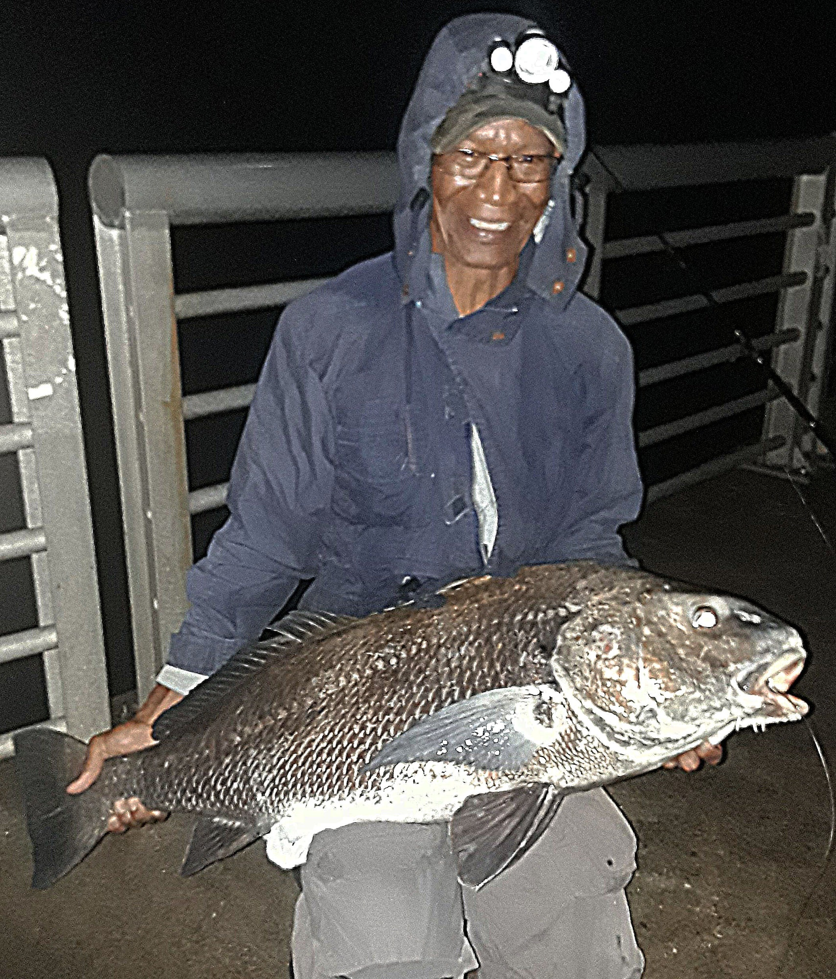 woman in rain coat with headlamp holding large fish
