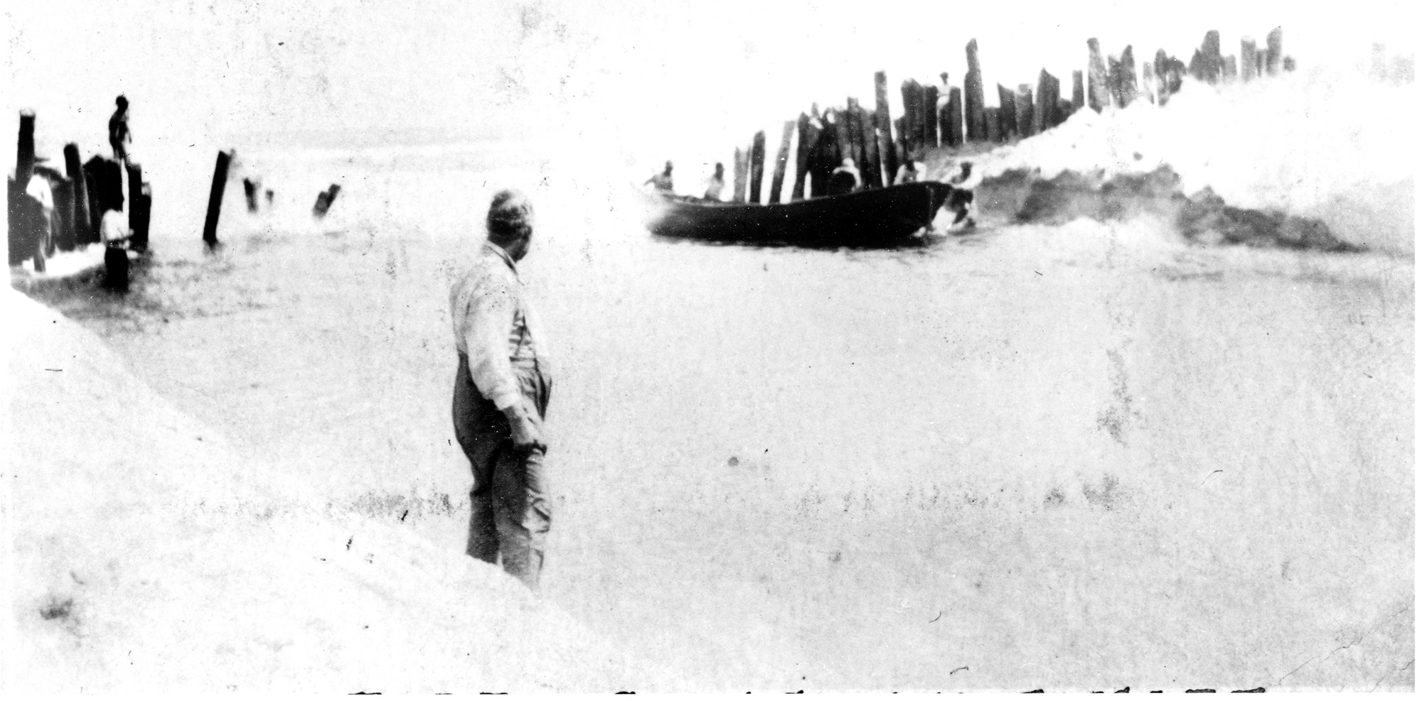 historical photo from 1918 showing a man standing in the foreground with a boat coming through the inlet