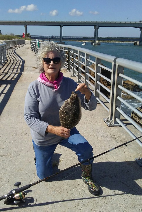 woman kneeling with fishing rod and holding flounder on jetty