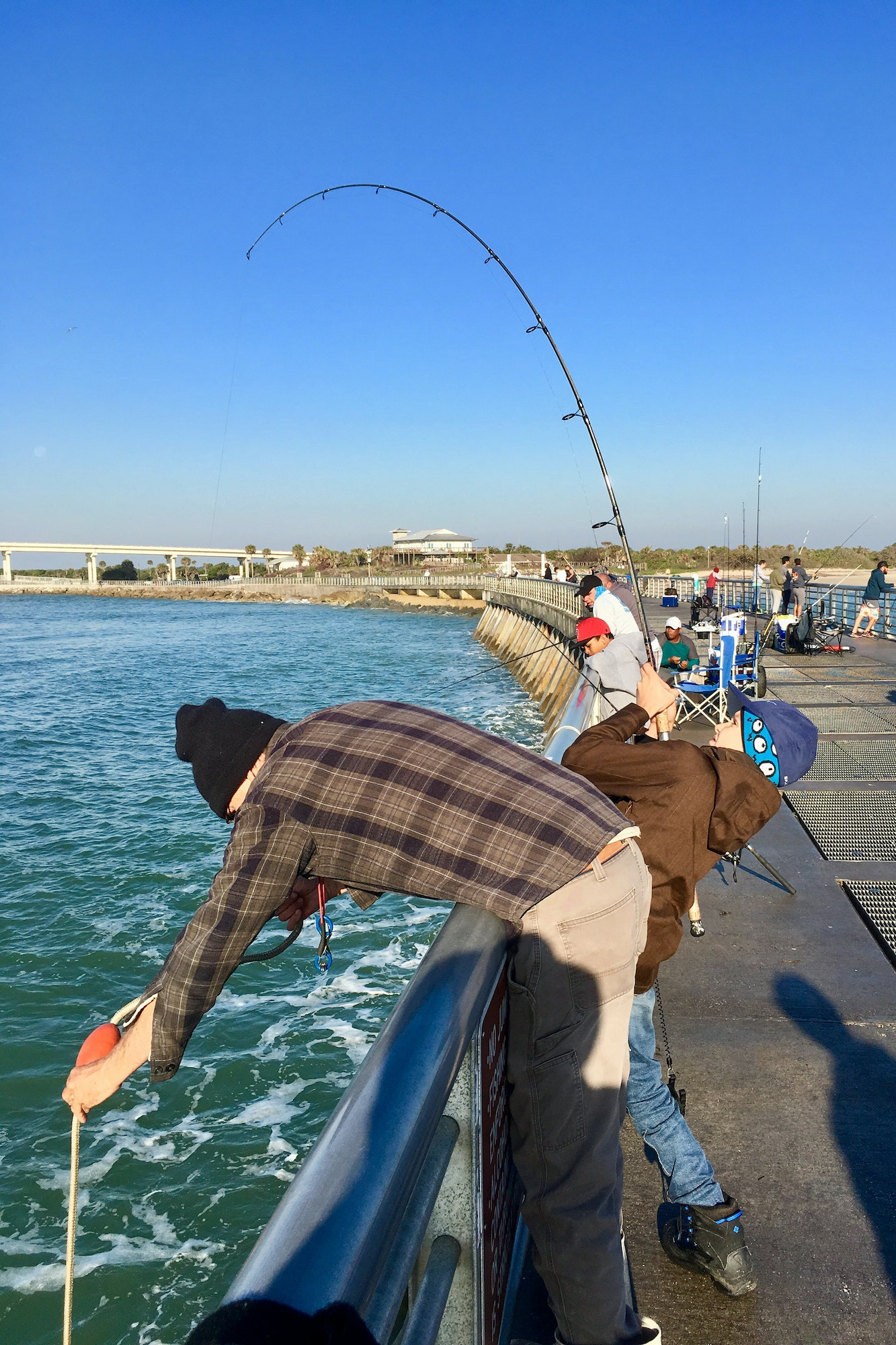 Young boy with fishing rod on North Jetty reeling in a fish