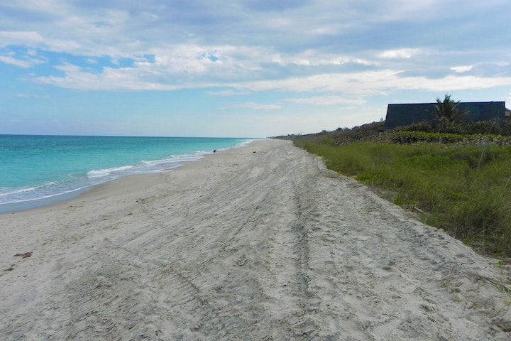 view of beach showing Atlantic Ocean with house on dune
