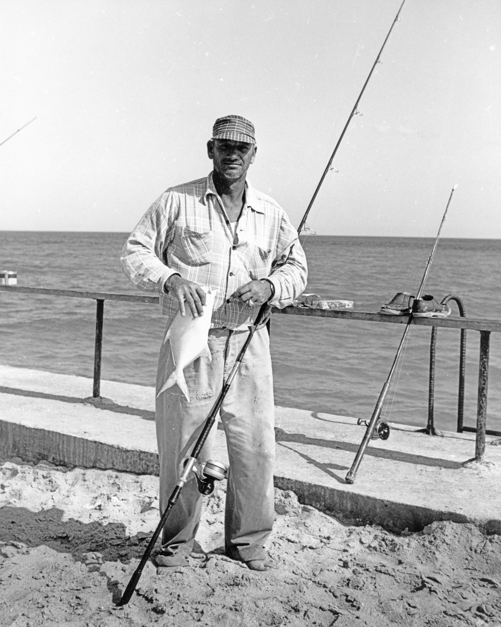 Fisherman standing with his rod and fish he caught on the jetty