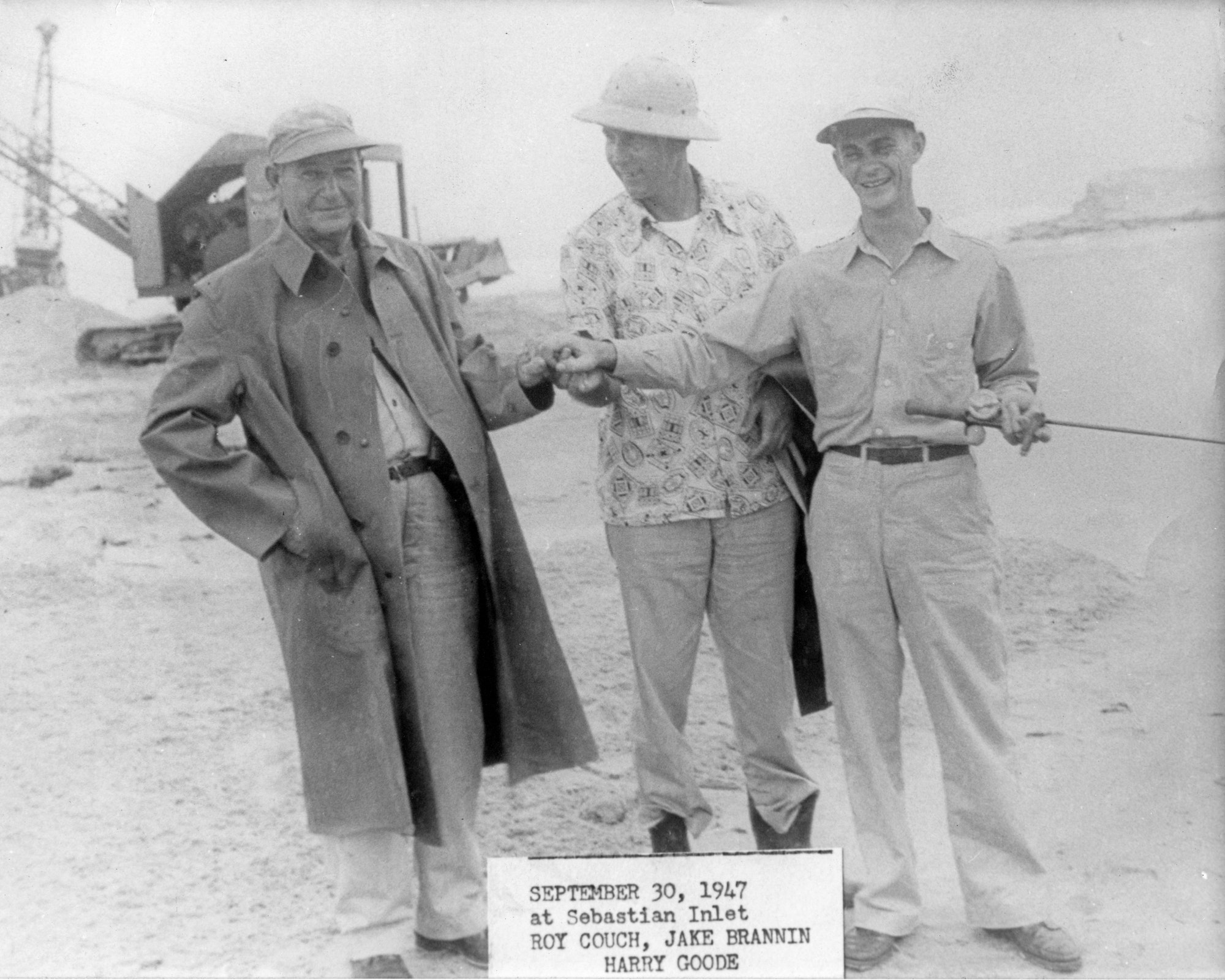 Three men standing together with an excavator in the background from 1947