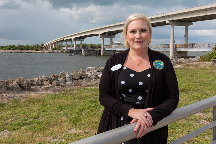 woman standing in front of sebastian inlet and bridge