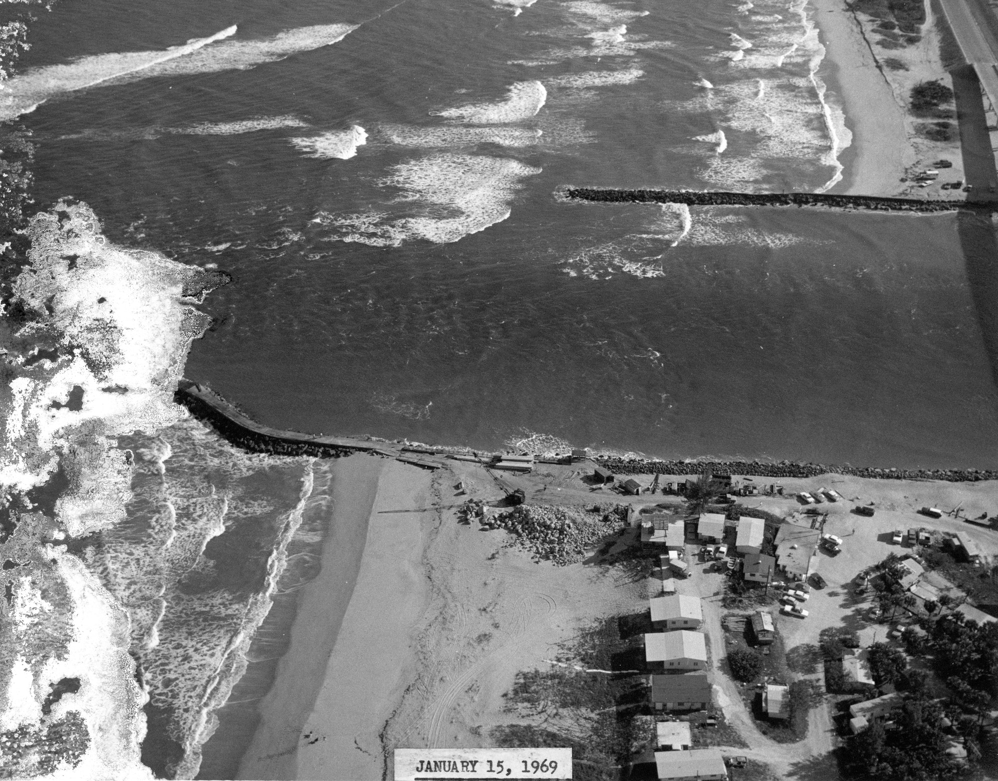 aerial view of the inlet mouth showing homes on the northern shoreline and construction staging area for north jetty and south jetty in background
