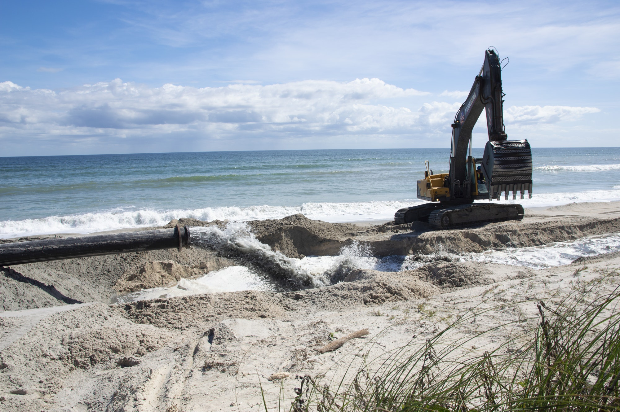 dredge pipe pumping water and sand into dike with heavy equipment