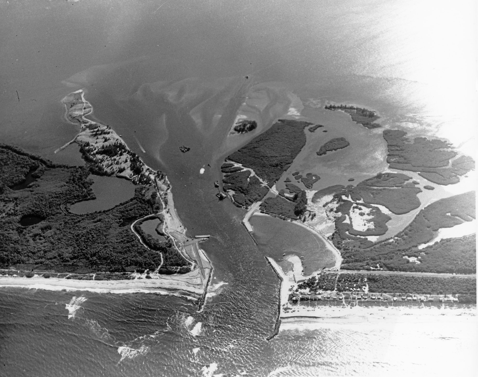 aerial view of the inlet in 1962 looking West with dredge boats and equipment removing sand