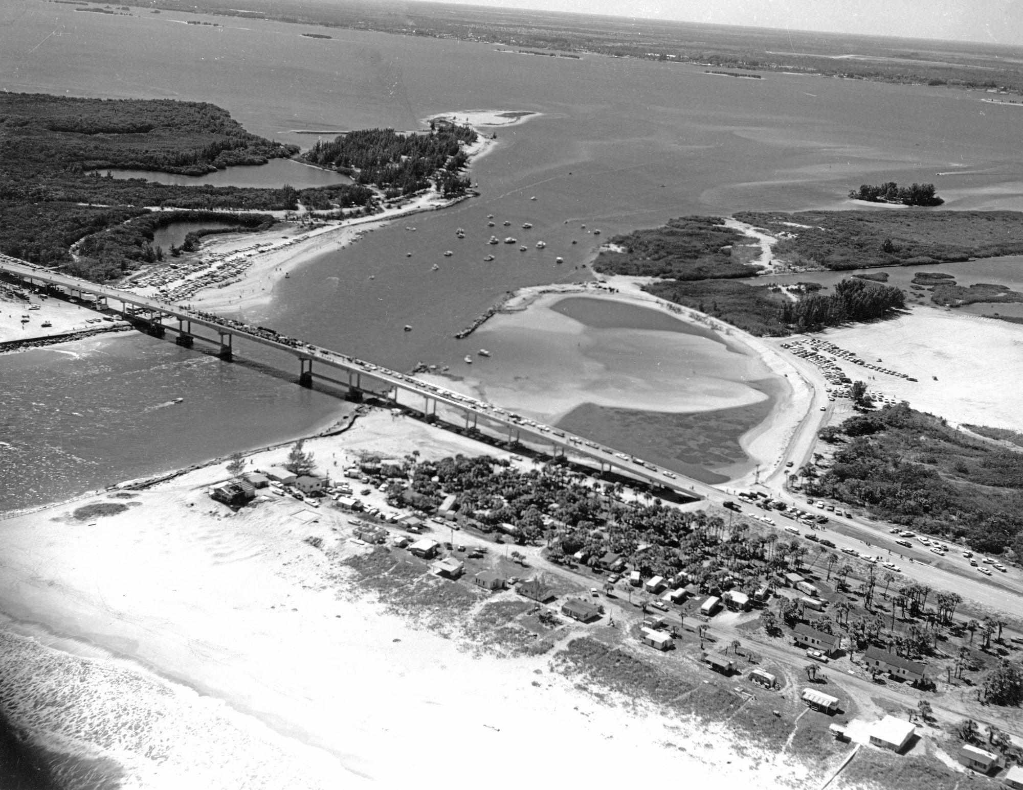 aerial view of the inlet looking Southwest showing completed bridge and spectator on opening day with Brevard County homesteads on the shore in foreground
