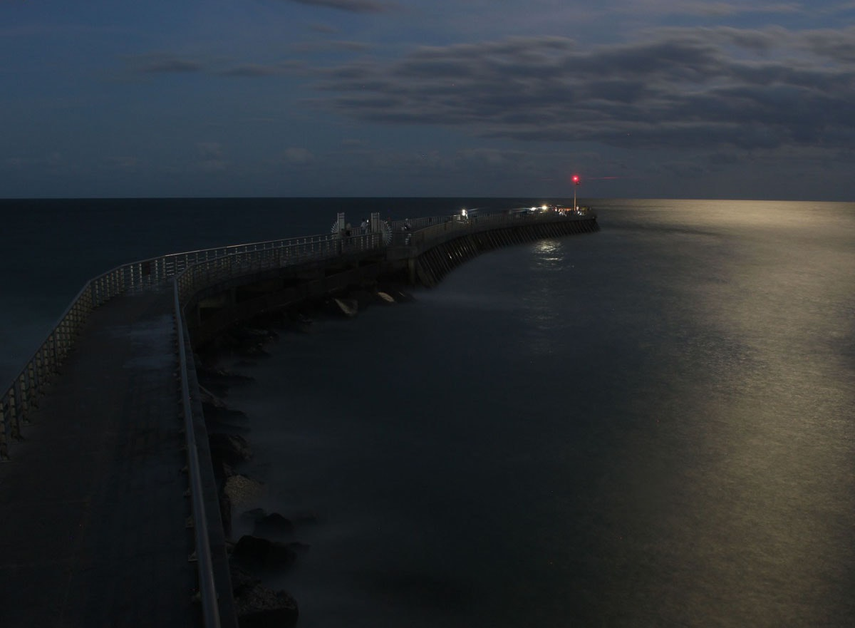 moonlight photo of north jetty with glowing red navigation light at tip