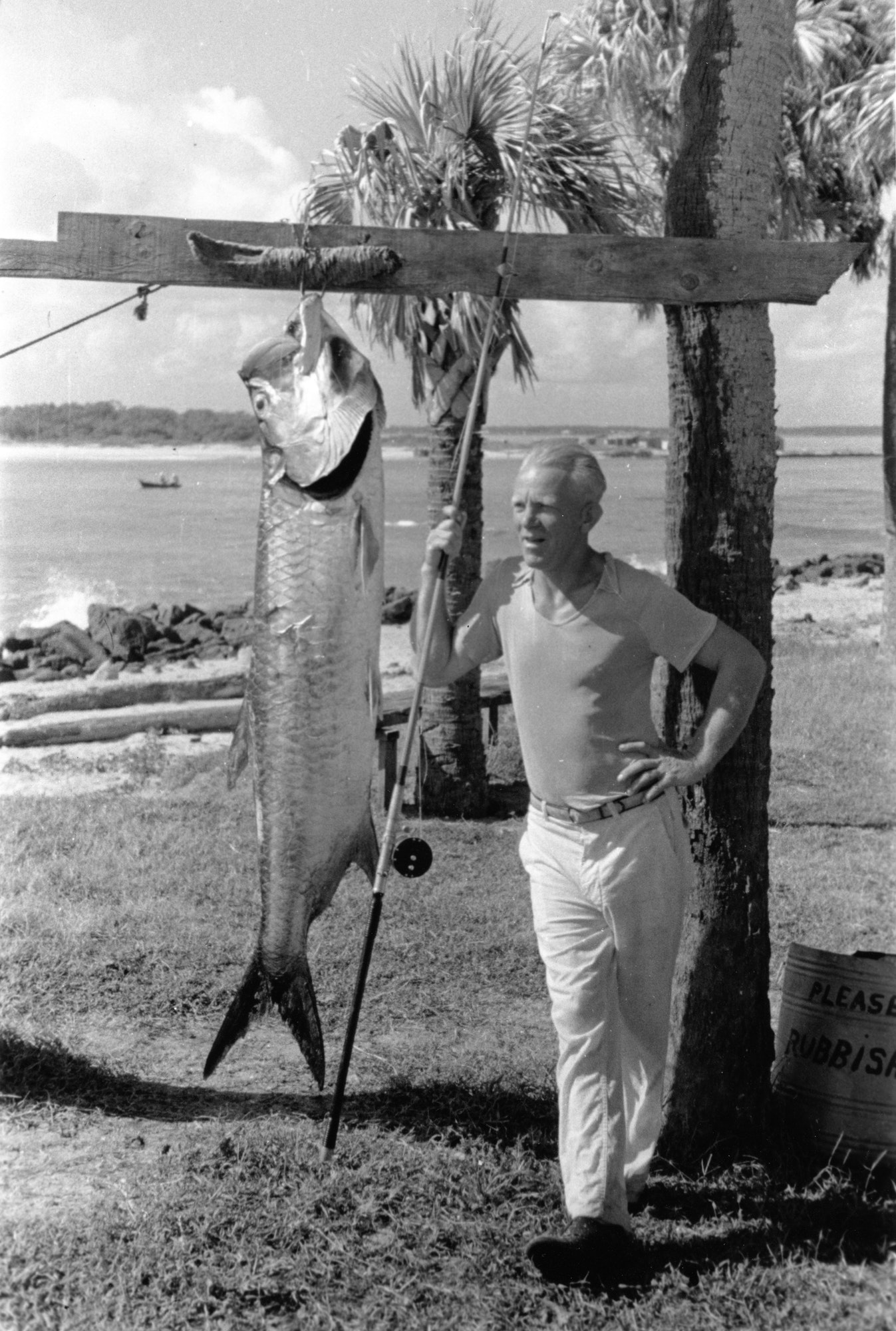 historical photo from mid-1930s of man displaying a massive tarpon caught fishing at the inlet