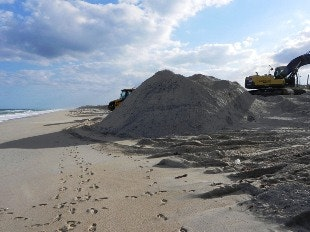 mound of sand on beach with heavy equipment