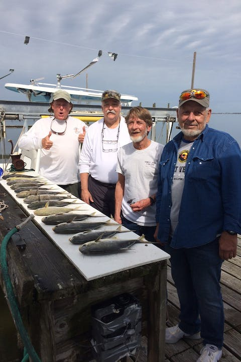 Four men standing behind a row of pompano on fish cleaning station