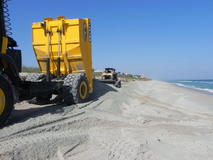 dump truck dumping sand onto beach