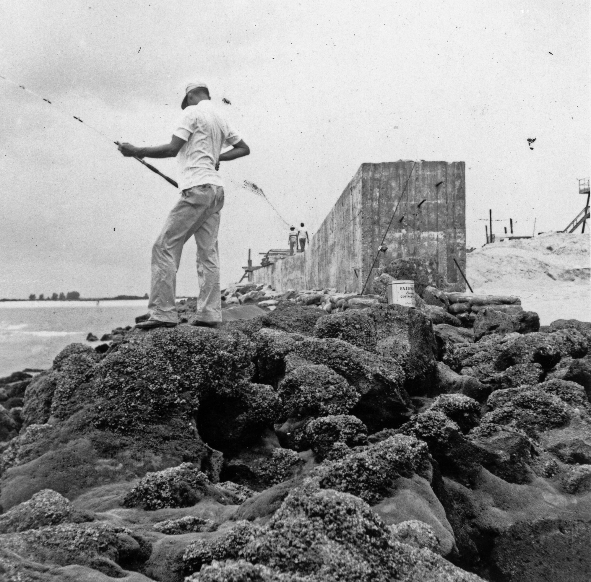 fisherman on the rocks in front of north jetty concrete cap