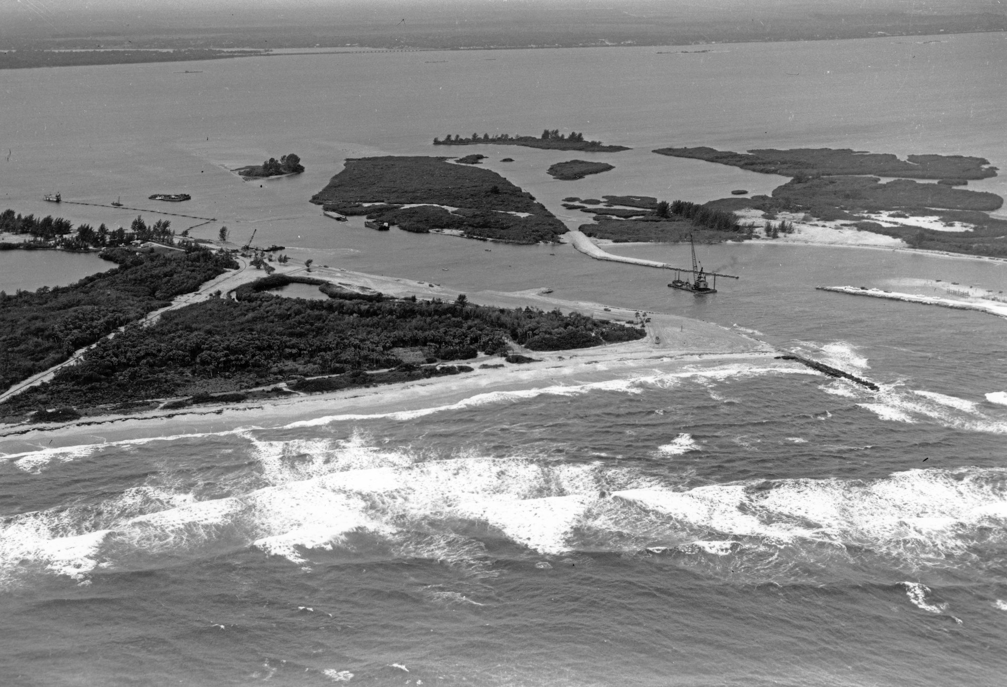 aerial view of the inlet in 1962 looking Northwest showing the south side of the inlet with dredge boats and equipment removing sand in the inlet channel