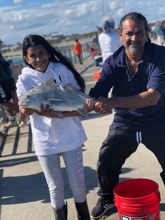 Young girl and father holding fish on north jetty