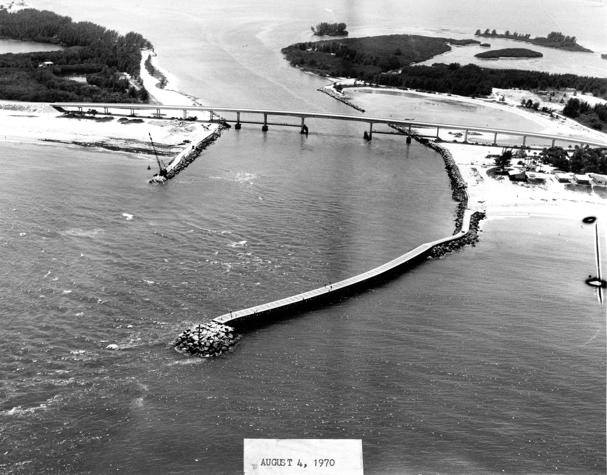 aerial view of inlet entrance looking West showing completed north jetty, construction work on south jetty and bridge
