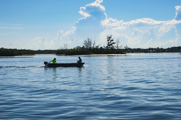 two men in skiff boat with small spoil island in background