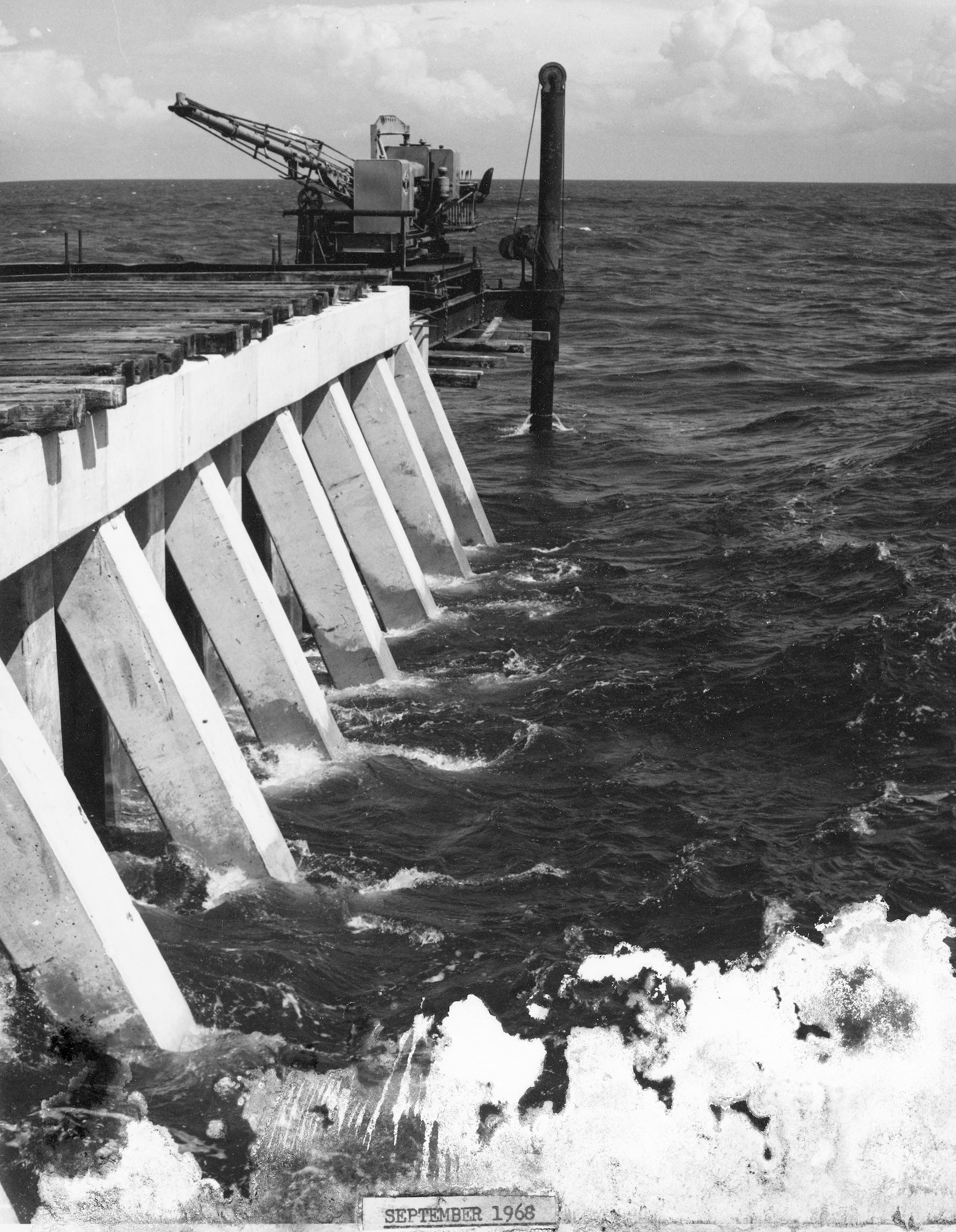 concrete crib structure of north jetty over the Atlantic Ocean with construction equipment at tip for installation of next section