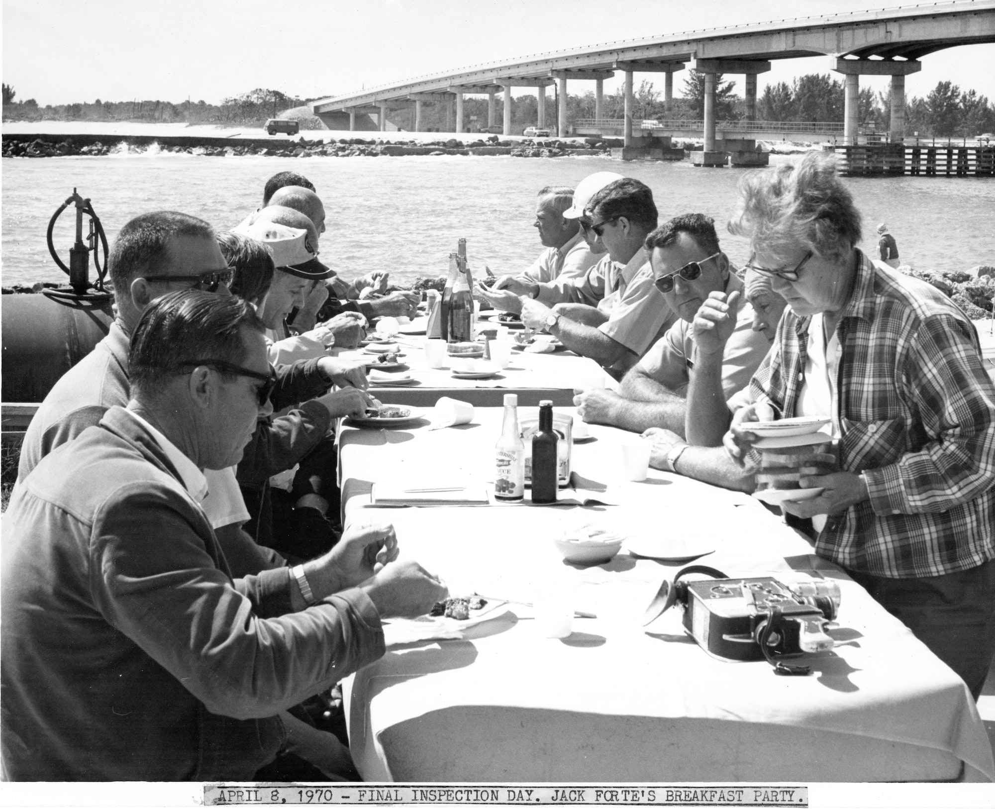 people gathered at a table for a meal with Sebastian Inlet bridge in background