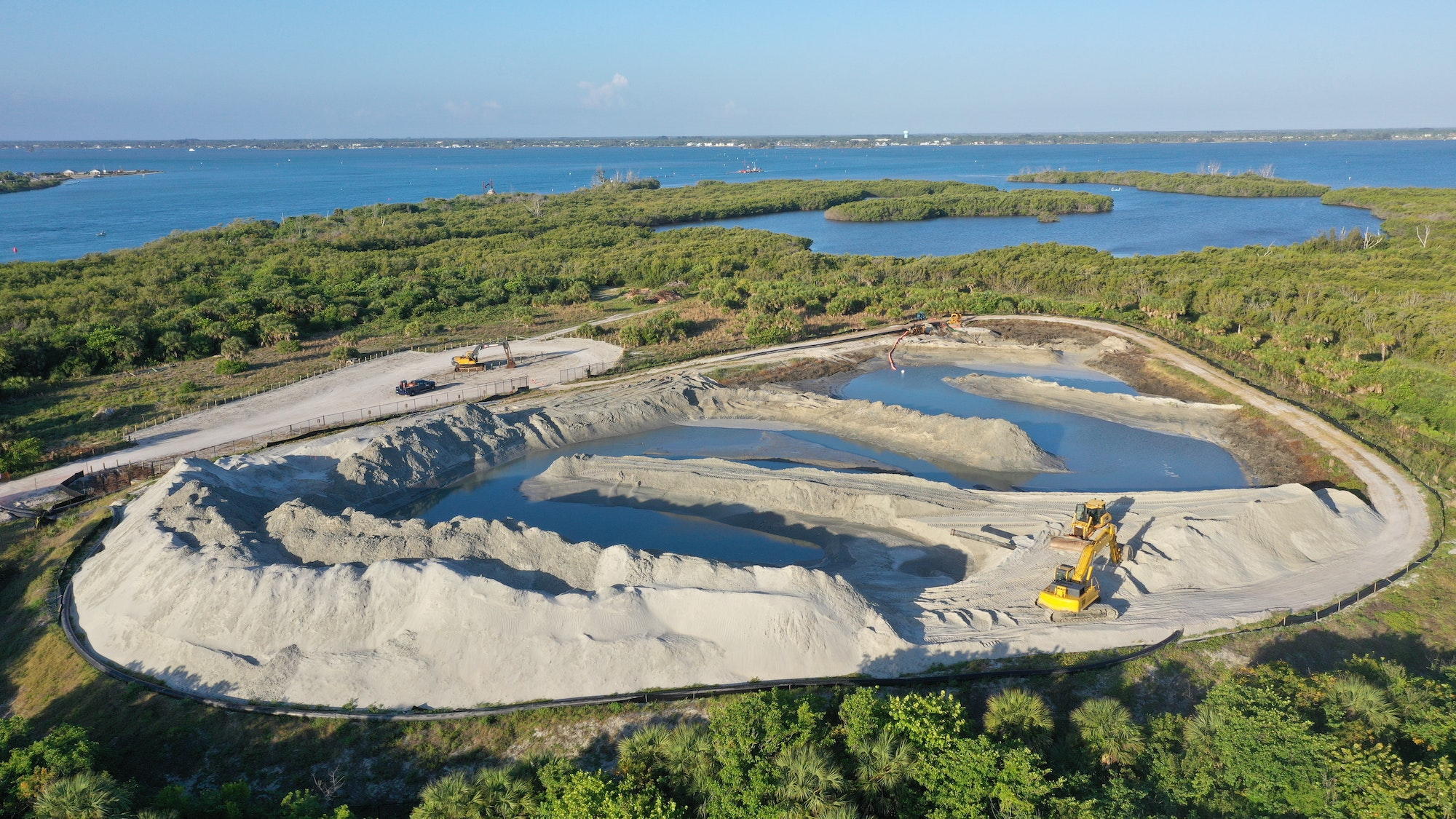 aerial view of equipment and mounds of sand in a sand storage site
