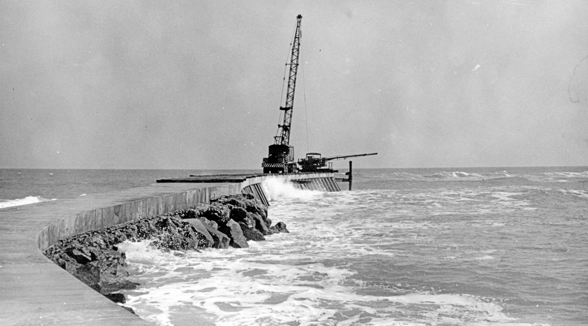 concrete and rocks of the north jetty over Atlantic Ocean waters with construction crane at tip of jetty