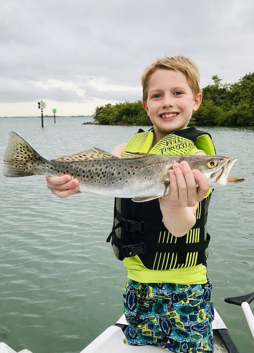 Young boy holding speckled sea trout