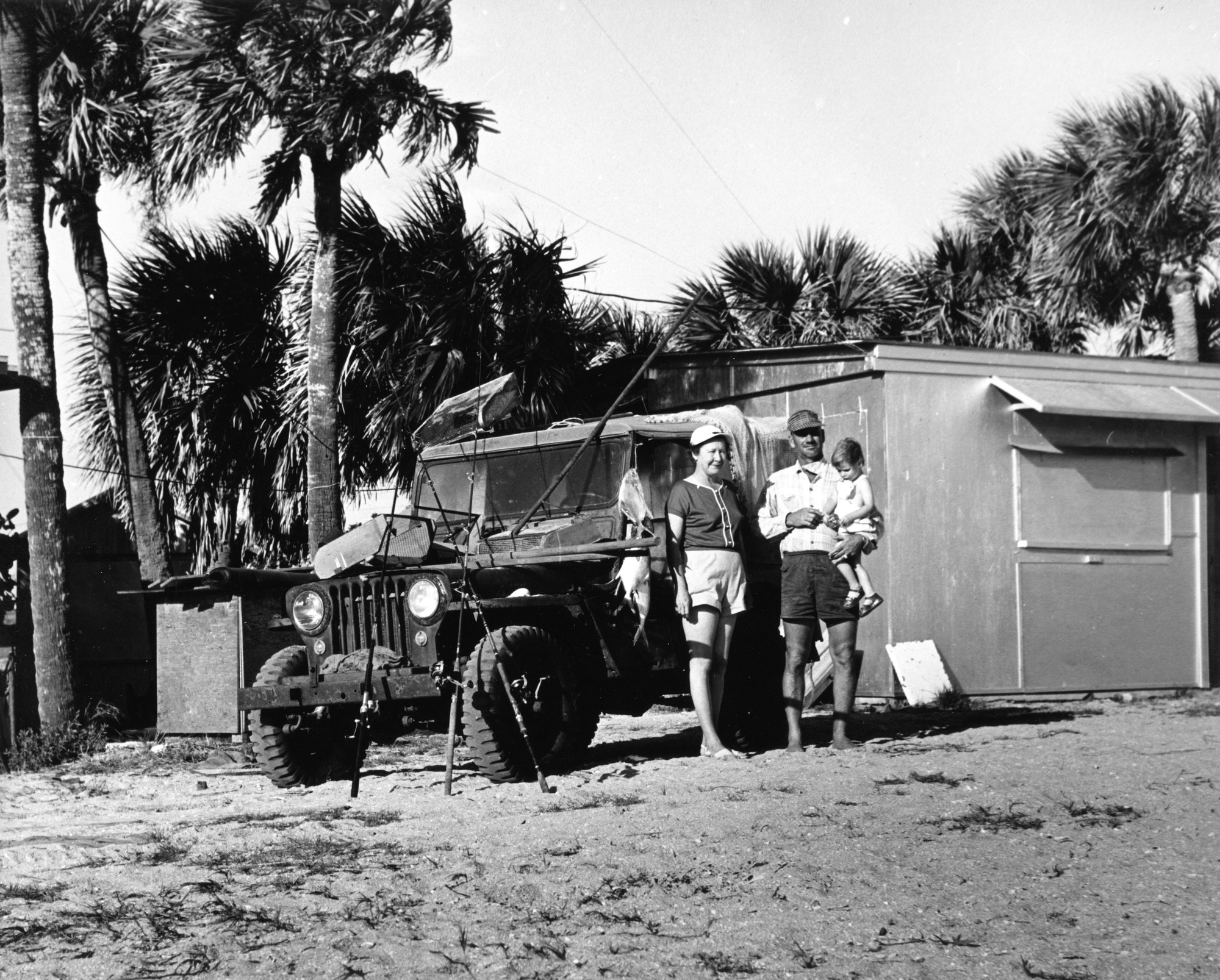 fisherman holding a small child with his wife and standing in front of jeep and shack at the inlet