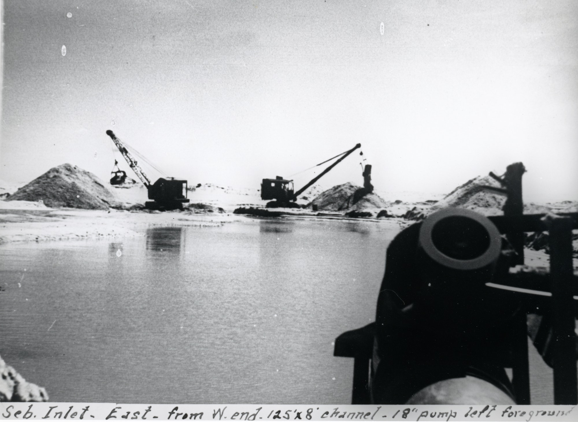 Two excavators moving sand in background with water and 18 inch pump in foreground