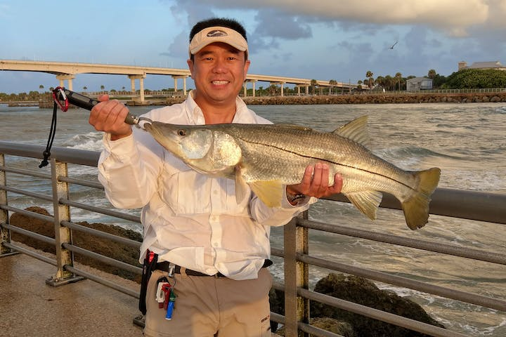 man holding large snook standing on jetty