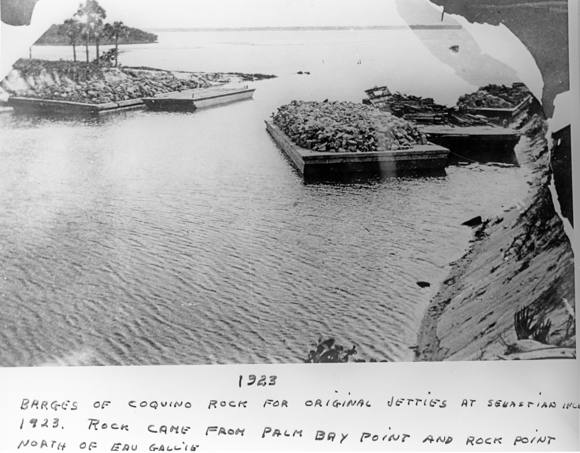 historical photo from 1923 showing barges carrying jetty rock and supplies at the inlet