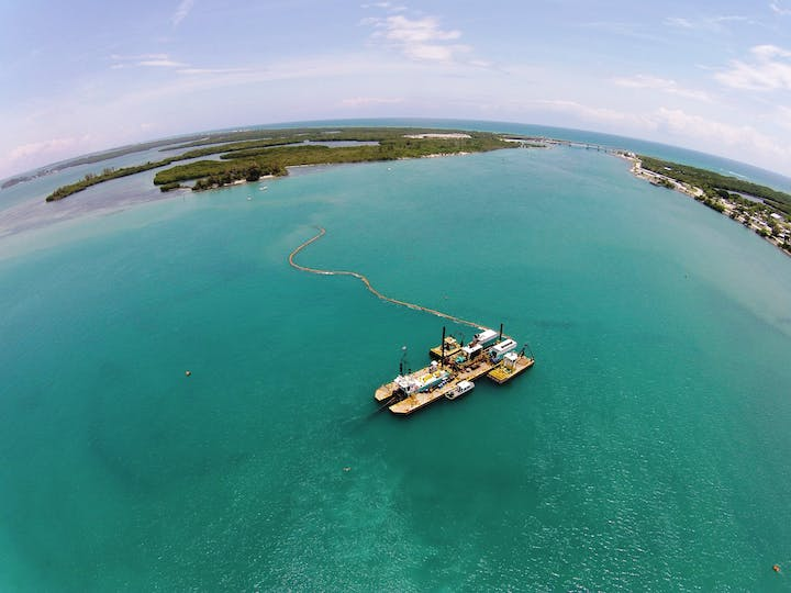 aerial view of dredge boat over sand trap in inlet channel