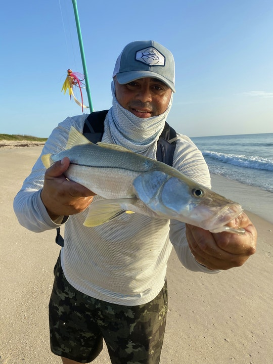 fisherman holding fish on beach