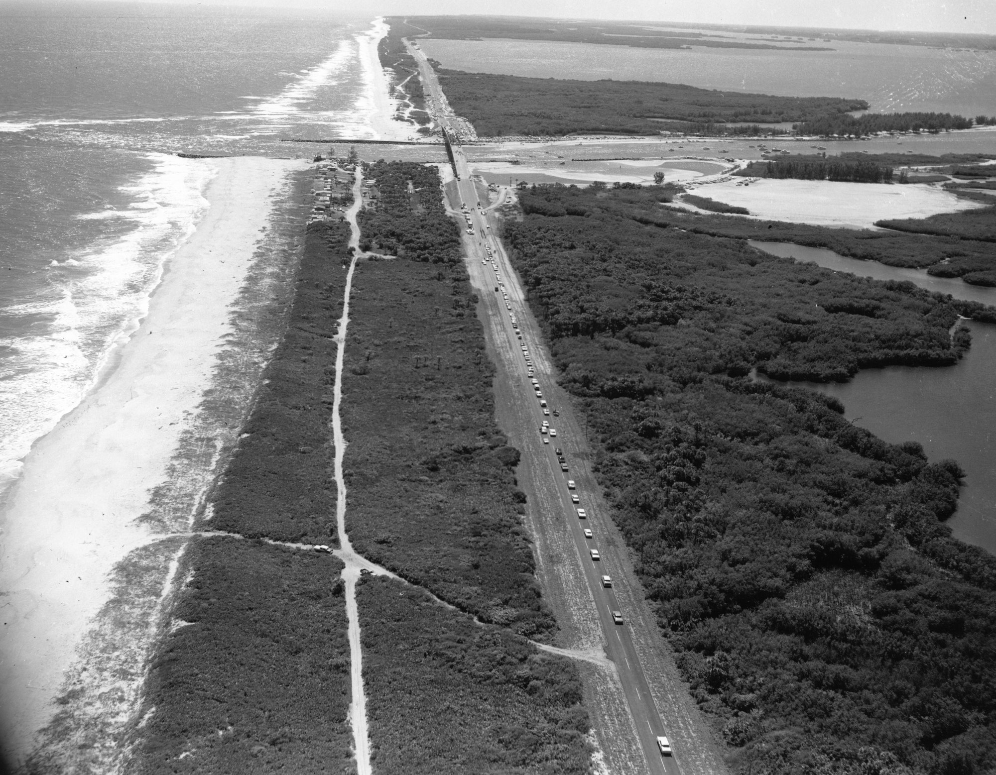aerial view of cars lined up on AIA headed South towards the inlet with shoreline and Atlantic Ocean on the left