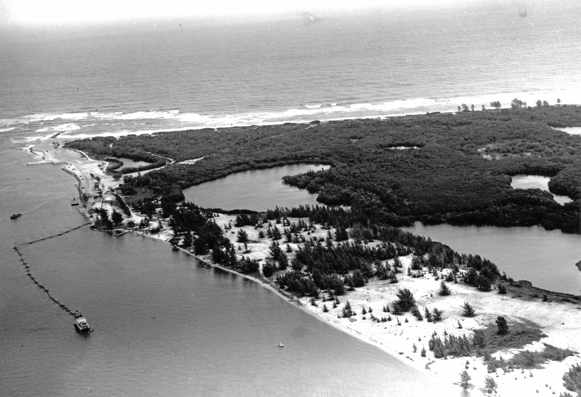 aerial view of the southern shoreline of the inlet with dredge and floating pipe