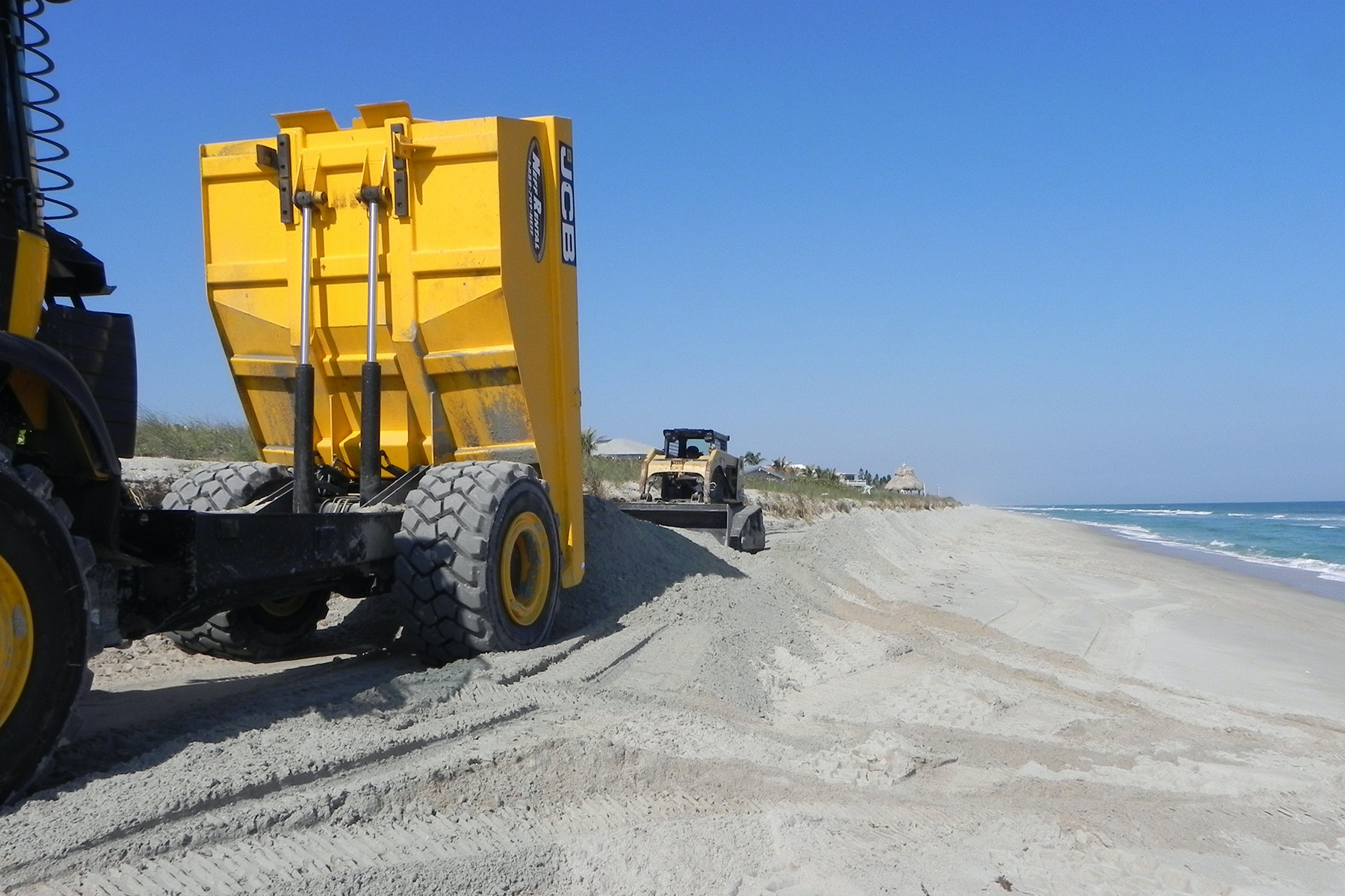 dump truck and bulldozer working to place sand on the beach